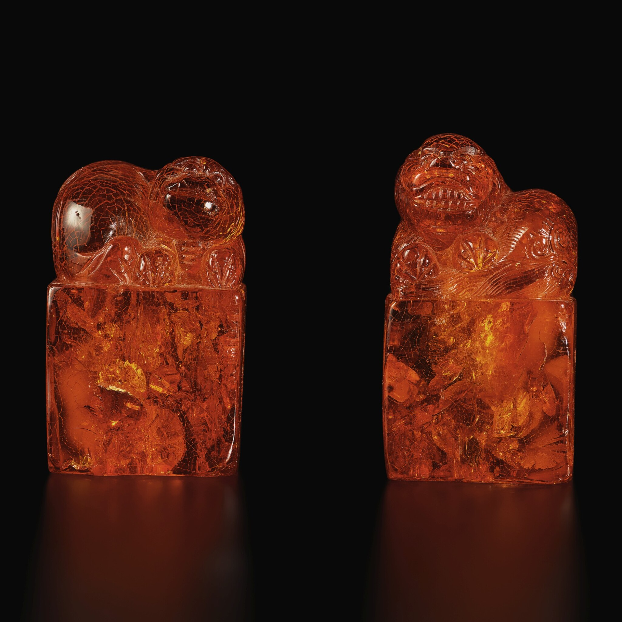 View full screen - View 1 of Lot 179. A pair of amber 'Buddhist lion' seals, Qing dynasty, 18th century | 清十八世紀 琥珀雕瑞獸鈕印料一對.