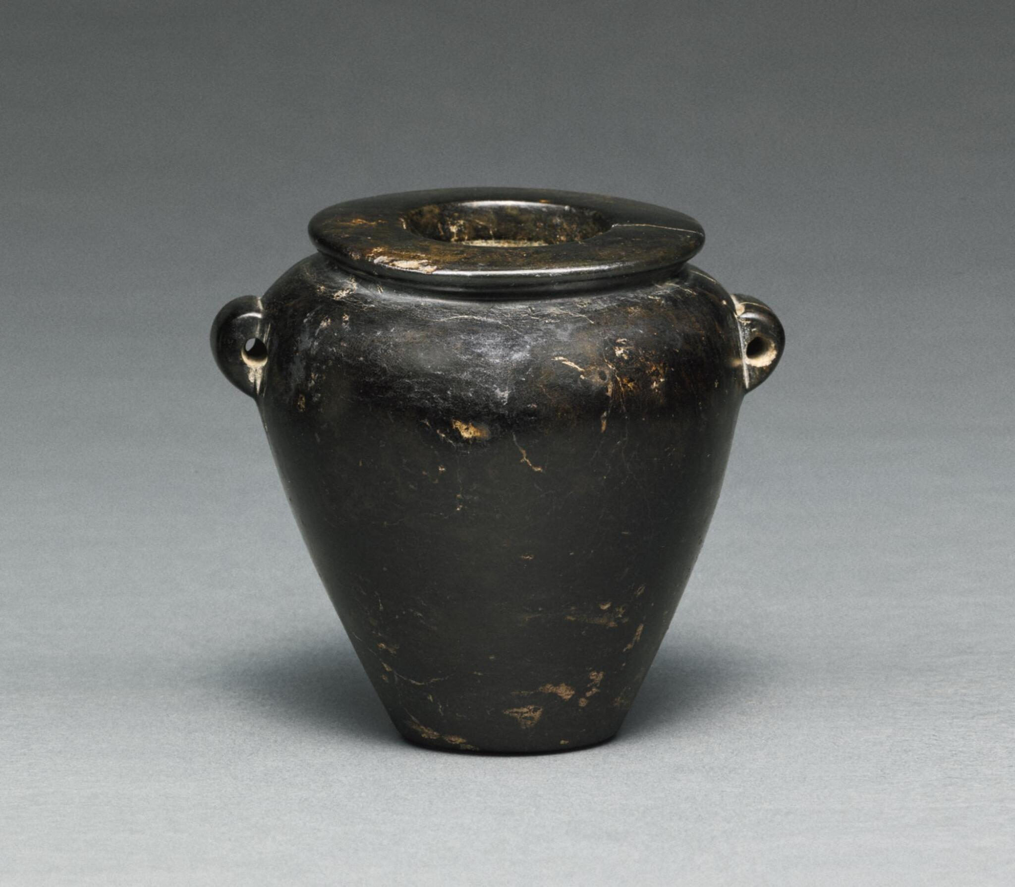 View full screen - View 1 of Lot 52. AN EGYPTIAN BROWN AND BLACK SERPENTINE JAR, LATE PREDYNASTIC PERIOD, CIRCA 3500-3200 B.C..