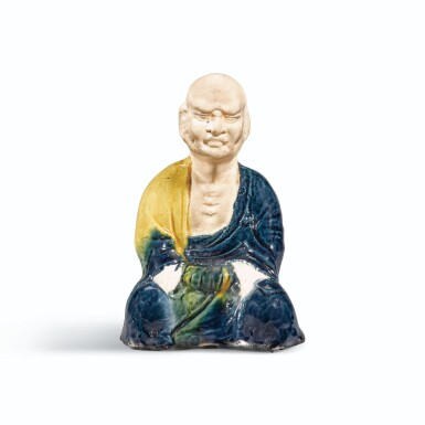 A RARE BLUE AND AMBER-GLAZED SEATED FIGURE OF A LUOHAN, TANG DYNASTY | 唐 藍釉羅漢坐像