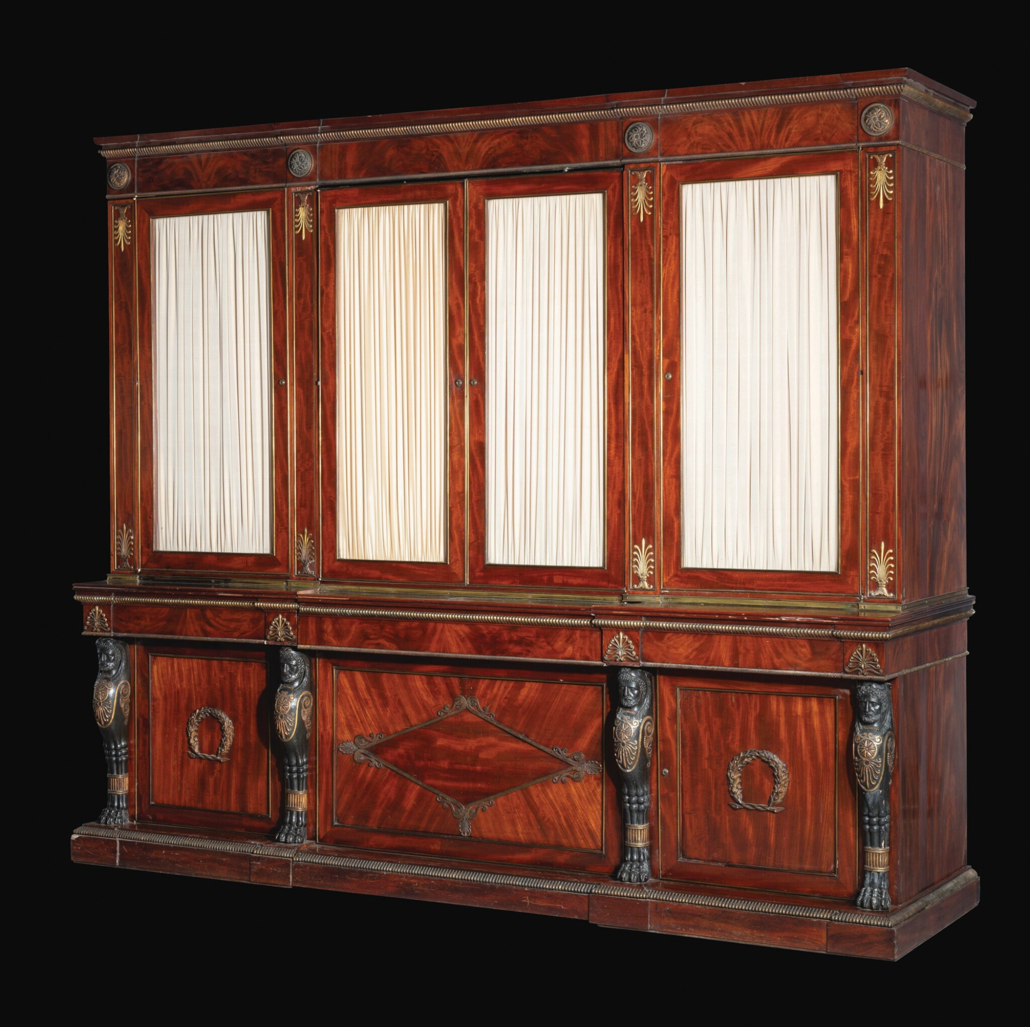 View full screen - View 1 of Lot 28. A late George III gilt-bronze mounted mahogany library bookcase incorporating a concealed door, circa 1805-10, attributed to Marsh and Tatham after designs by Thomas Hope.