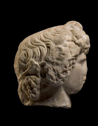 View 2. Thumbnail of Lot 251. A MONUMENTAL ROMAN MARBLE PORTRAIT HEAD OF ANTINOUS AS DIONYSOS-OSIRIS, CIRCA A.D. 130–138.