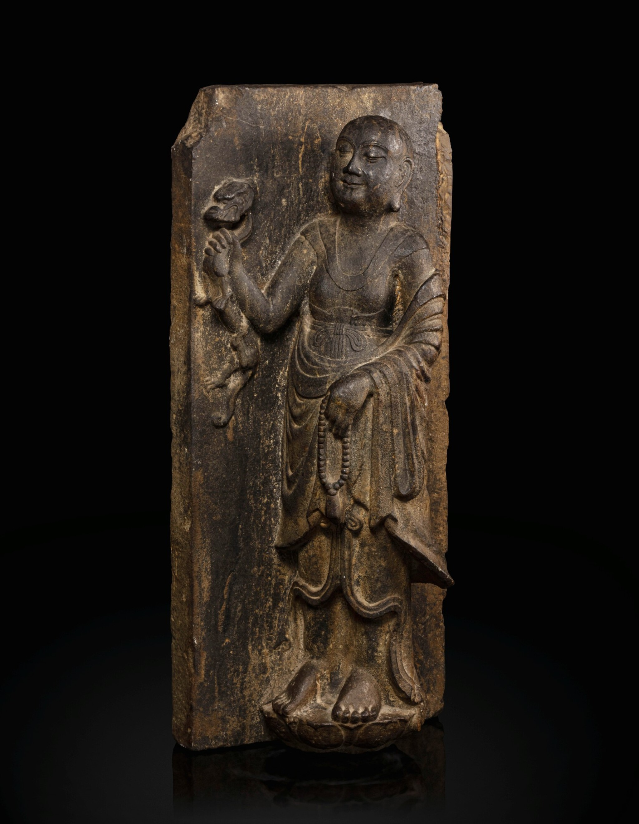 View full screen - View 1 of Lot 51. A rare limestone carving of a Buddhist acolyte, possibly Jianglong Luohan Northern Song dynasty, 10th-11th century   北宋十至十一世紀 石灰石浮雕或為降龍羅漢像.