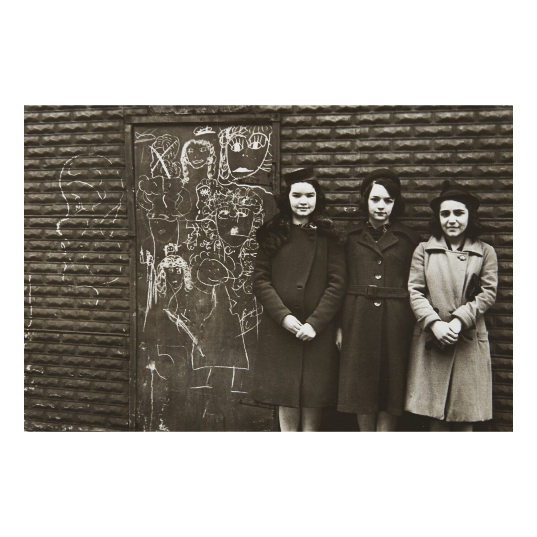 View full screen - View 1 of Lot 155. HELEN LEVITT | THREE YOUNG WOMEN AGAINST WALL WITH CHALK DRAWING.