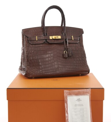 View 2. Thumbnail of Lot 20. Matte havanne niloticus crocodile, canvas and gold plated hardware handbag, Birkin 35, Hermès, 2002.