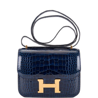 View 1. Thumbnail of Lot 3. Hermès Bleu Saphir Constance 18cm of Shiny Alligator with Gold Hardware.