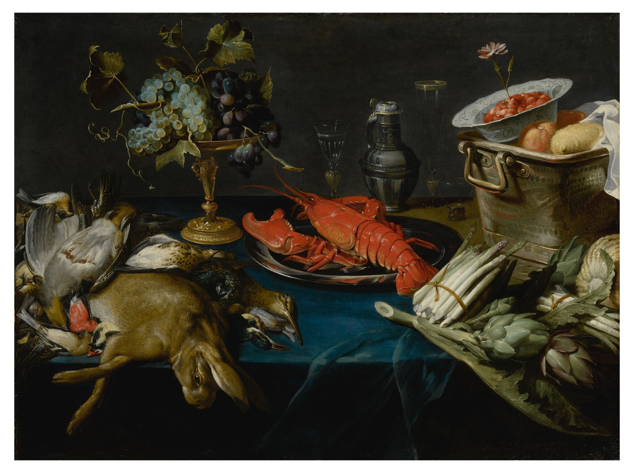 WORKSHOP OF FRANS SNIJDERS | STILL LIFE WITH A LOBSTER ON A SILVER DISH, A DEAD HARE AND OTHER GAME, BLUE AND WHITE GRAPES ON A SILVER-GILT TAZZA, ARTICHOKES, ASPARAGUS, A WAN-LI KRAAK BOWL WITH STRAWBERRIES IN A COPPER BUCKET, ALL ARRANGED ON A TABLE DRAPED WITH A BLUE VELVET CLOTH
