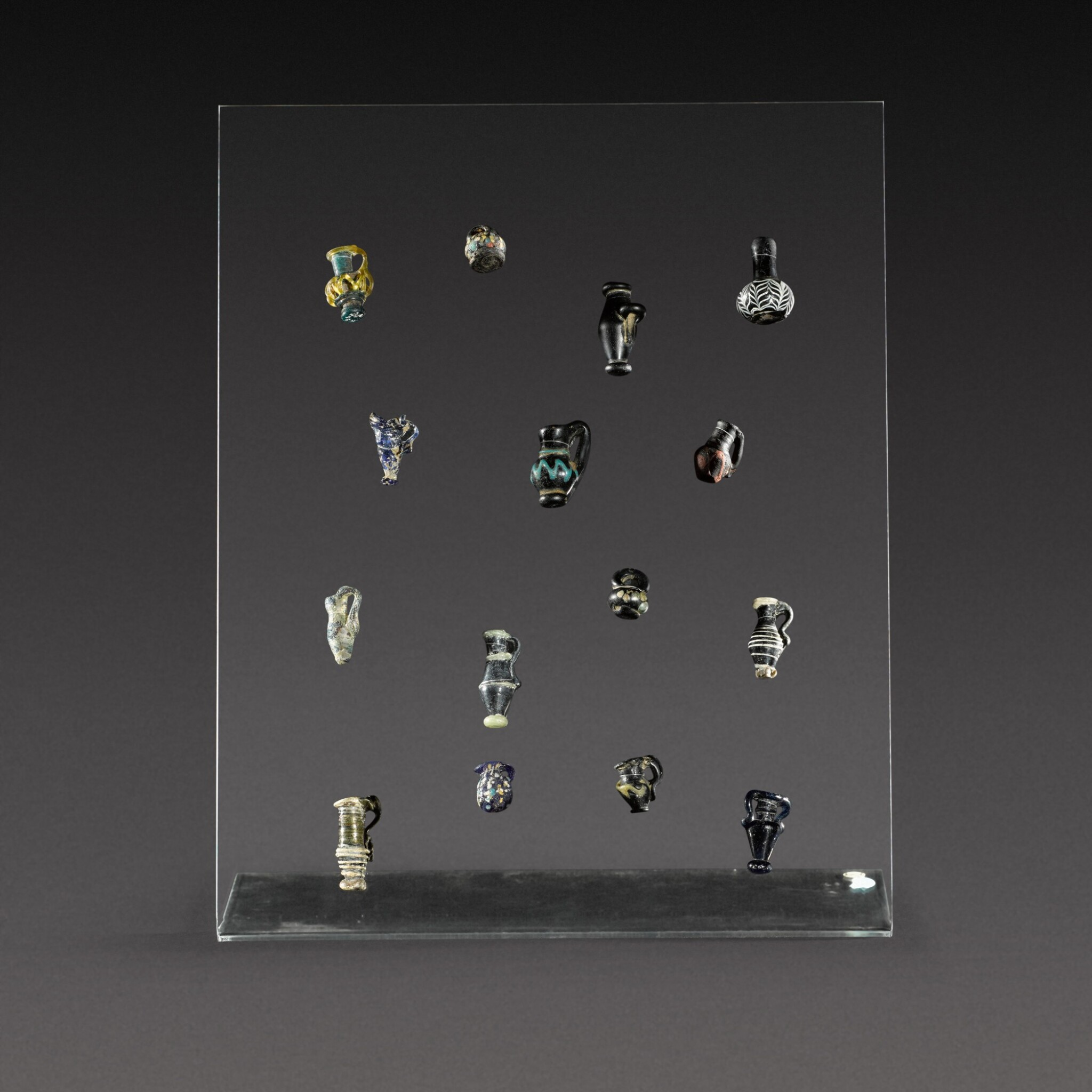 View full screen - View 1 of Lot 11. A Group of Fifteen Roman Miniature Glass Vessels, circa 1st/4th century A.D..