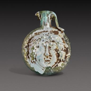 View 1. Thumbnail of Lot 1. A Roman Pale Green Mould-Blown Janiform Glass Flask, circa 1st/2nd century A.D..