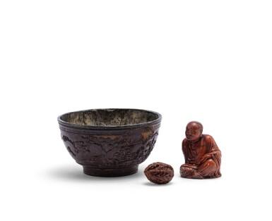 View 1. Thumbnail of Lot 161. Bol en noix de coco sculpté, noix sculptée, et, figure d'immortel en stéatite sculptée Dynastie Qing | 清 雜項一組三件 | A pewter-lined 'deers in a landscape' coconut bowl, a finely carved 'eight immortal' nut, and a soapstone figure of a luohan, Qing Dynasty  .