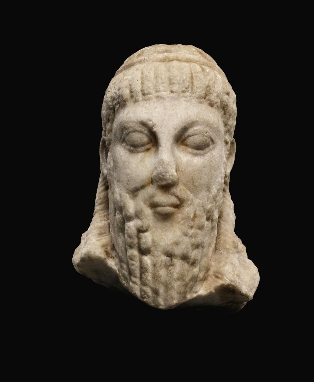A ROMAN MARBLE ARCHAISTIC HERM HEAD OF DIONYSOS, CIRCA 2ND CENTURY A.D.