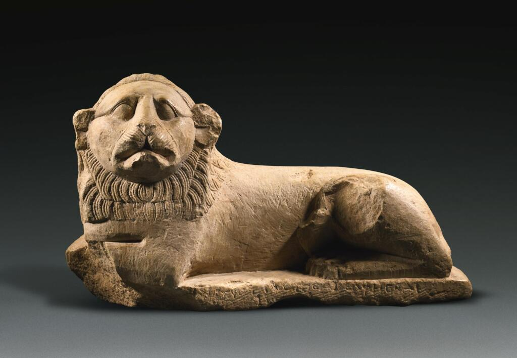 AN EGYPTIAN INDURATED LIMESTONE FIGURE OF A LION, PTOLEMAIC PERIOD, LAST QUARTER OF THE 3RD CENTURY B.C.