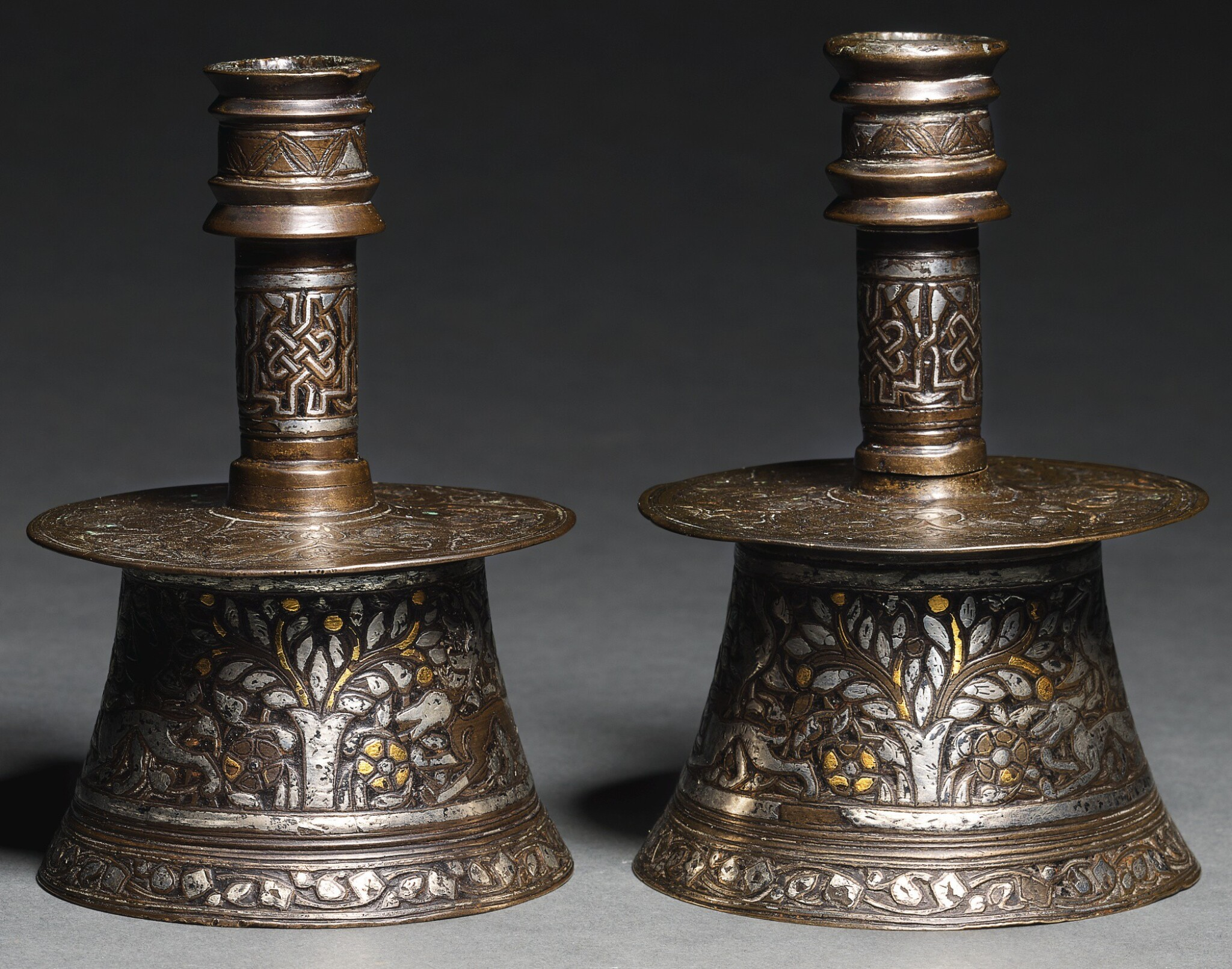 View full screen - View 1 of Lot 103. TWO MINIATURE MAMLUK SILVER AND GOLD-INLAID BRASS CANDLESTICKS, EGYPT OR SYRIA, EARLY 15TH CENTURY.