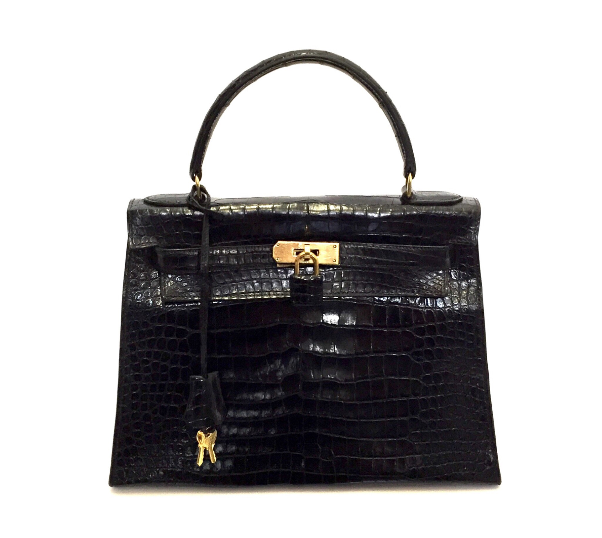 View full screen - View 1 of Lot 743. HERMÈS | BLACK KELLY 28 IN SHINY CROCODILE WITH GOLD HARDWARE, 1962.