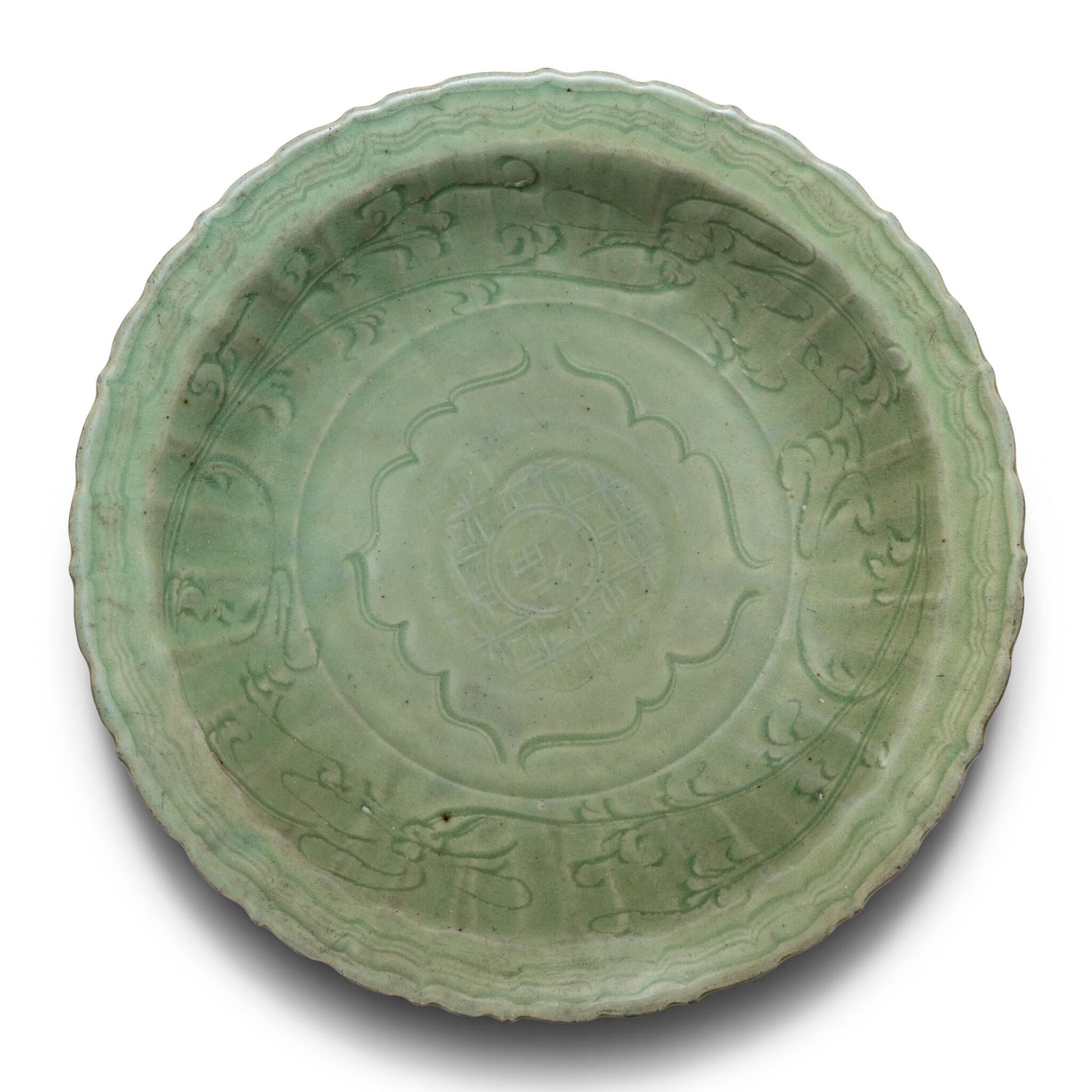 View 1 of Lot 12. Plat en grès céladon Longquan Dynastie Ming   明 龍泉窰青釉刻花菱口折沿盤   A Longqan celadon charger, Ming Dynasty.