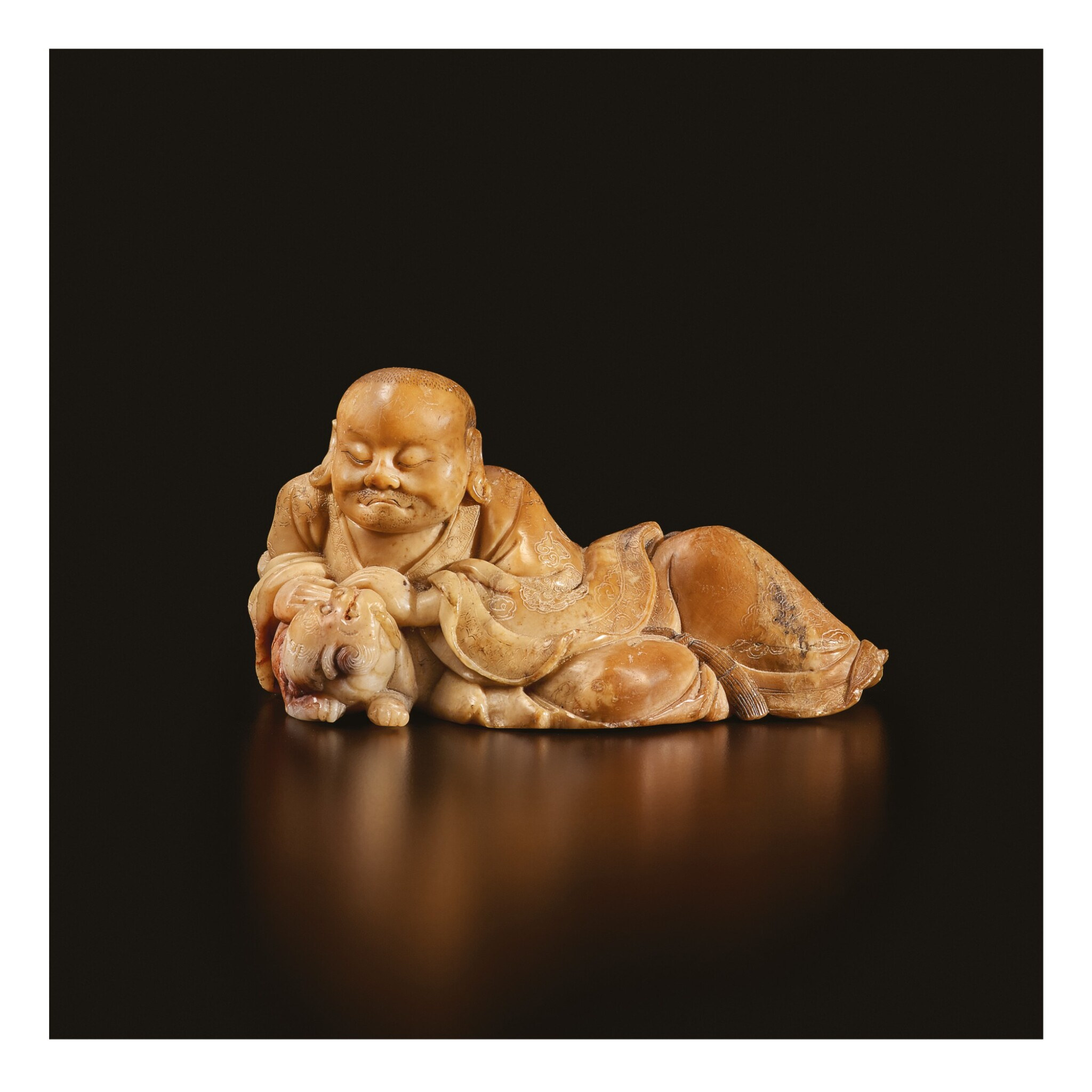 View full screen - View 1 of Lot 671. A BEIGE SOAPSTONE FIGURE OF A RECLINING LUOHAN, 17TH / 18TH CENTURY.