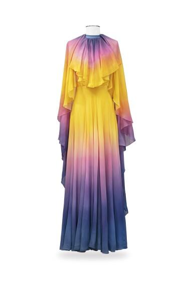 View 1. Thumbnail of Lot 10. Balestra, 1972, Sunbathing dress with pleated collar and matching cape | Robe longue bain de soleil à collerette plissée en mousseline avec cape assortie.