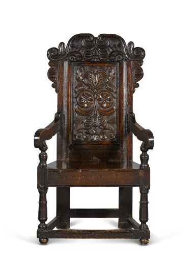 View 1. Thumbnail of Lot 24. A Charles II carved oak panel-back armchair.