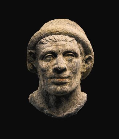 AN ETRUSCAN NENFRO PORTRAIT HEAD OF A MAN, LATE 2ND/EARLY 1ST CENTURY B.C.