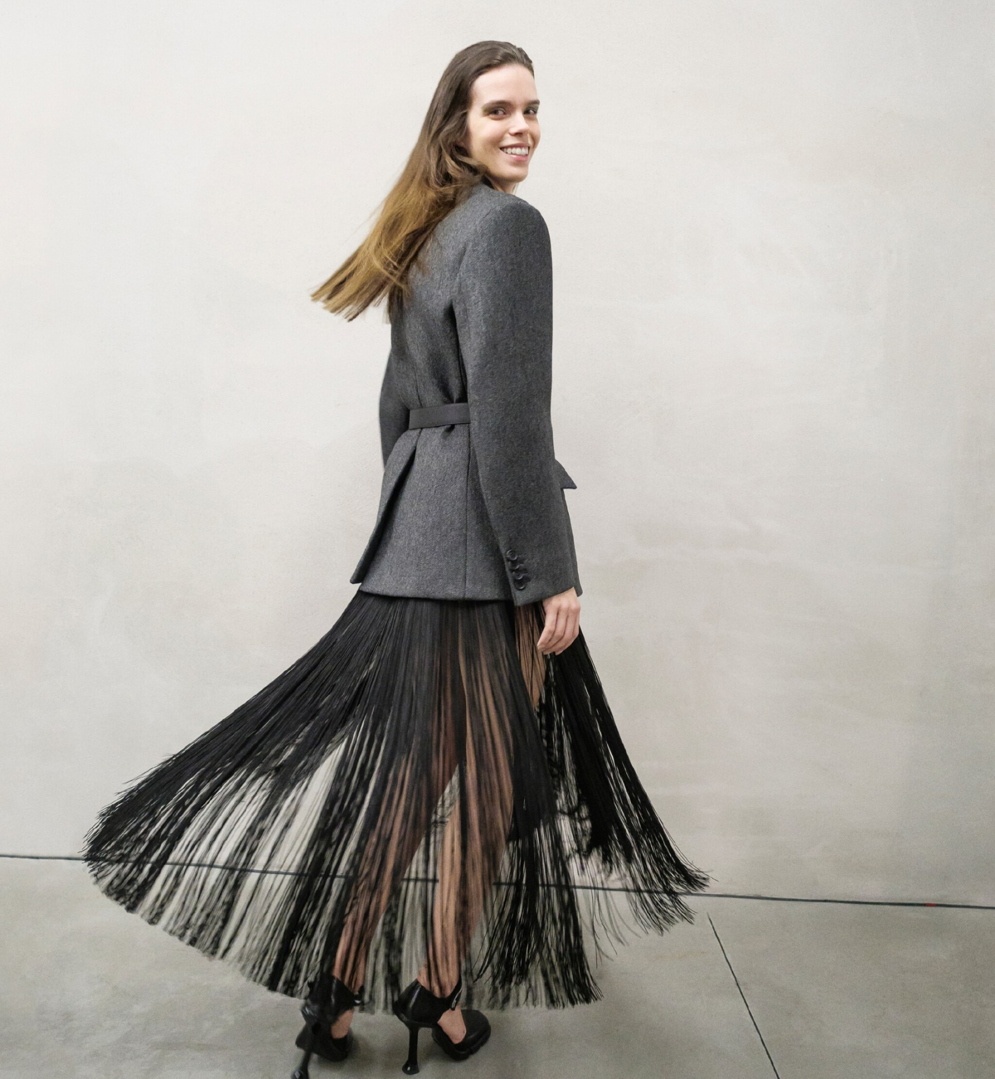 View full screen - View 1 of Lot 13. PRADA   OPENING LOOK OF THE SHOW.  FLUID FRINGE DRESS, WOOL JACKET, VANITY BELT, BRUSHED LEATHER PUMPS, WORN BY MEGHAN COLLISON.