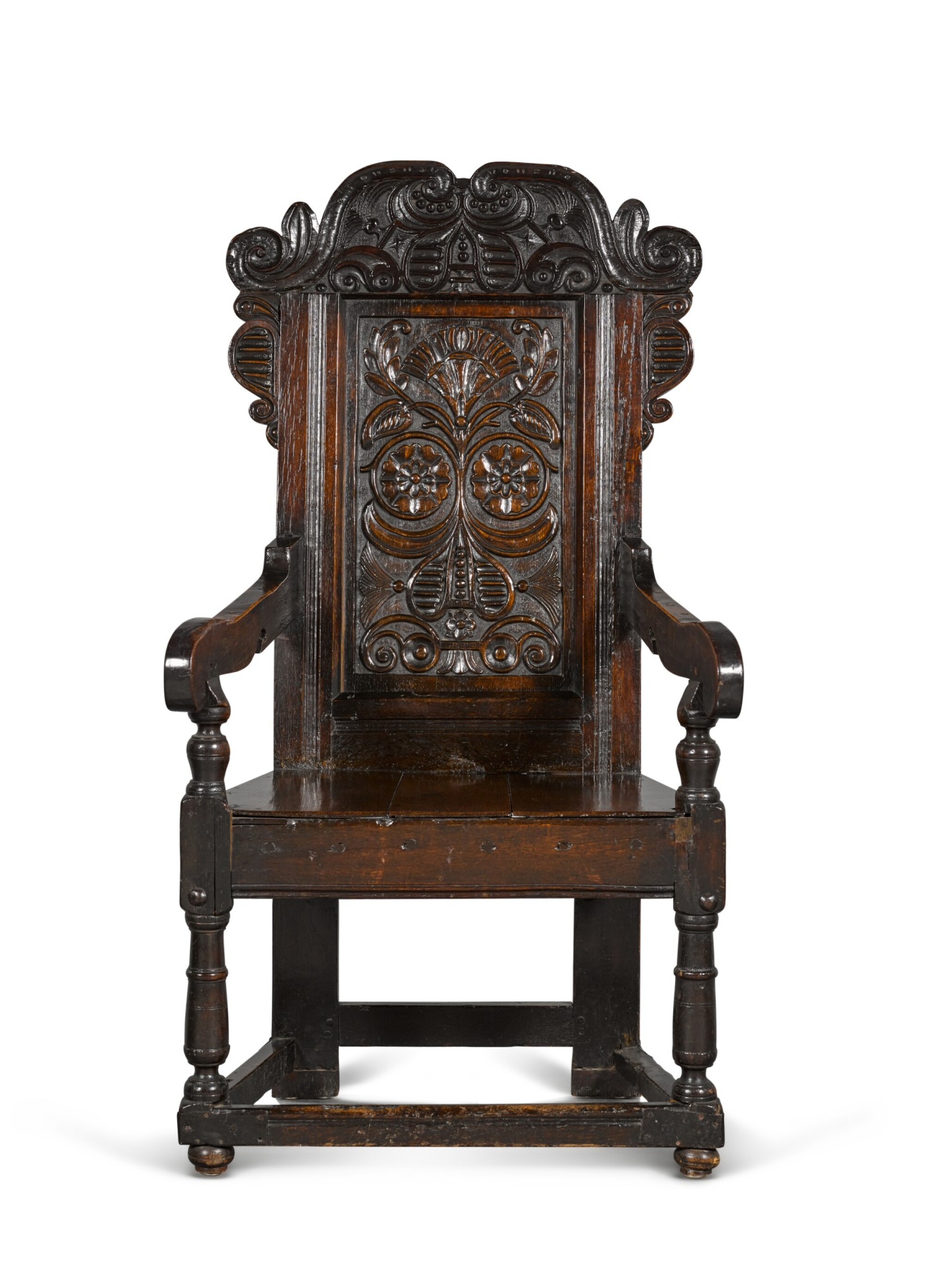 View 1 of Lot 24. A Charles II carved oak panel-back armchair.