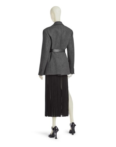 View 3. Thumbnail of Lot 13. PRADA   OPENING LOOK OF THE SHOW.  FLUID FRINGE DRESS, WOOL JACKET, VANITY BELT, BRUSHED LEATHER PUMPS, WORN BY MEGHAN COLLISON.