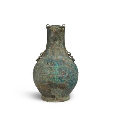 View 2. Thumbnail of Lot 18. An archaic bronze wine vessel and cover (Hu), Eastern Zhou dynasty, Warring States period   東周 戰國 青銅卷龍紋鋪首耳壺.
