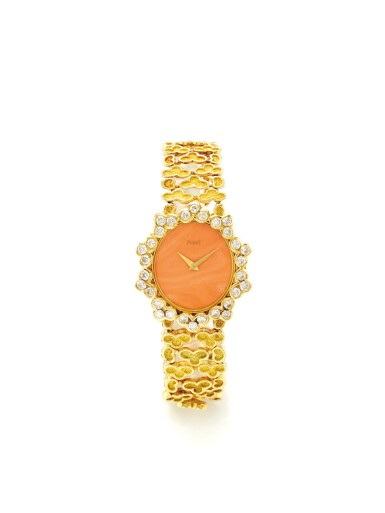 Lot 170 PIAGET | A YELLOW GOLD AND DIAMOND SET BRACELET WATCH WITH CORAL DIAL CIRCA 1975