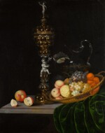 Still life with an elaborate silver gilt standing cup, a basket of fruit, and a glass wine jug upon a partly draped table