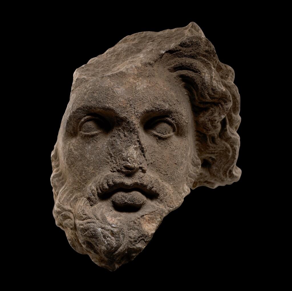 A HELLENISTIC MARBLE HEAD OF A BEARDED GOD, CIRCA 3RD CENTURY B.C.