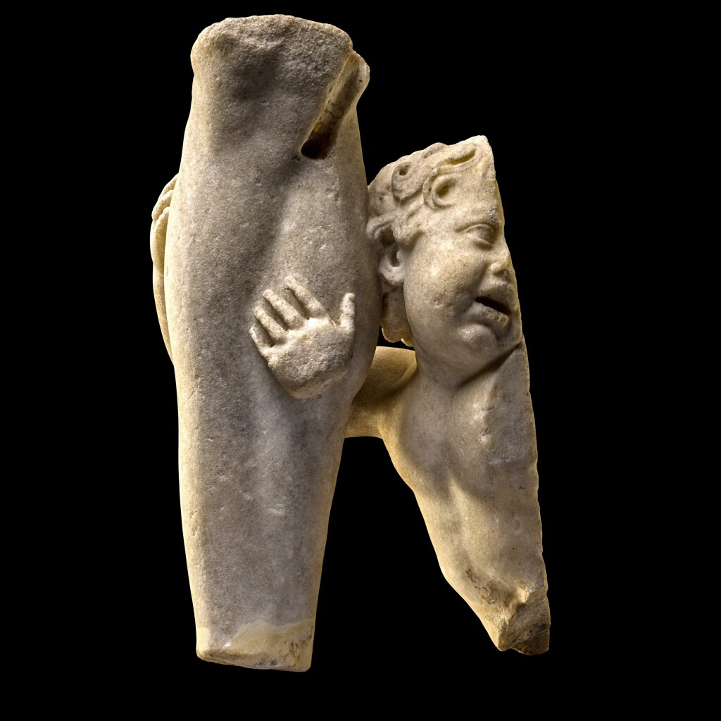 A ROMAN FRAGMENTARY MARBLE GROUP OF EROS EMBRACING THE LEG OF A GOD, CIRCA 2ND CENTURY A.D.