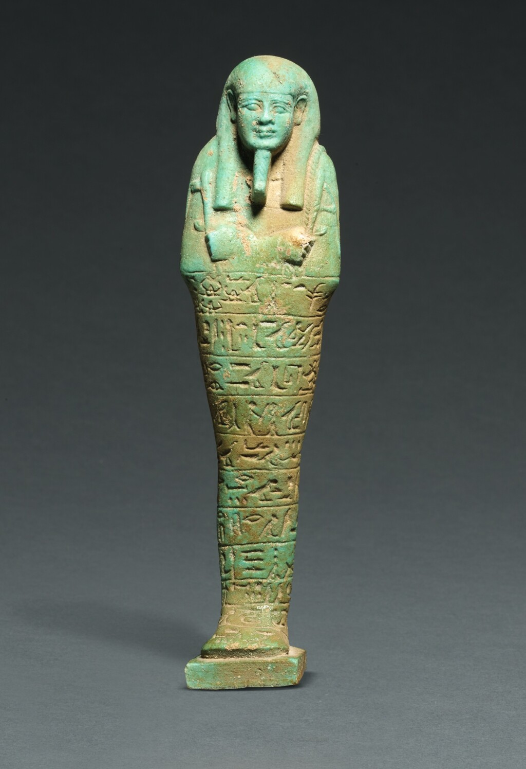 AN EGYPTIAN TURQUOISE-BLUE FAIENCE USHABTI OF TJAI-NE-HEBU, ADMIRAL OF THE ROYAL FLEET, 26TH DYNASTY, REIGN OF AMASIS, 570-526 B.C.