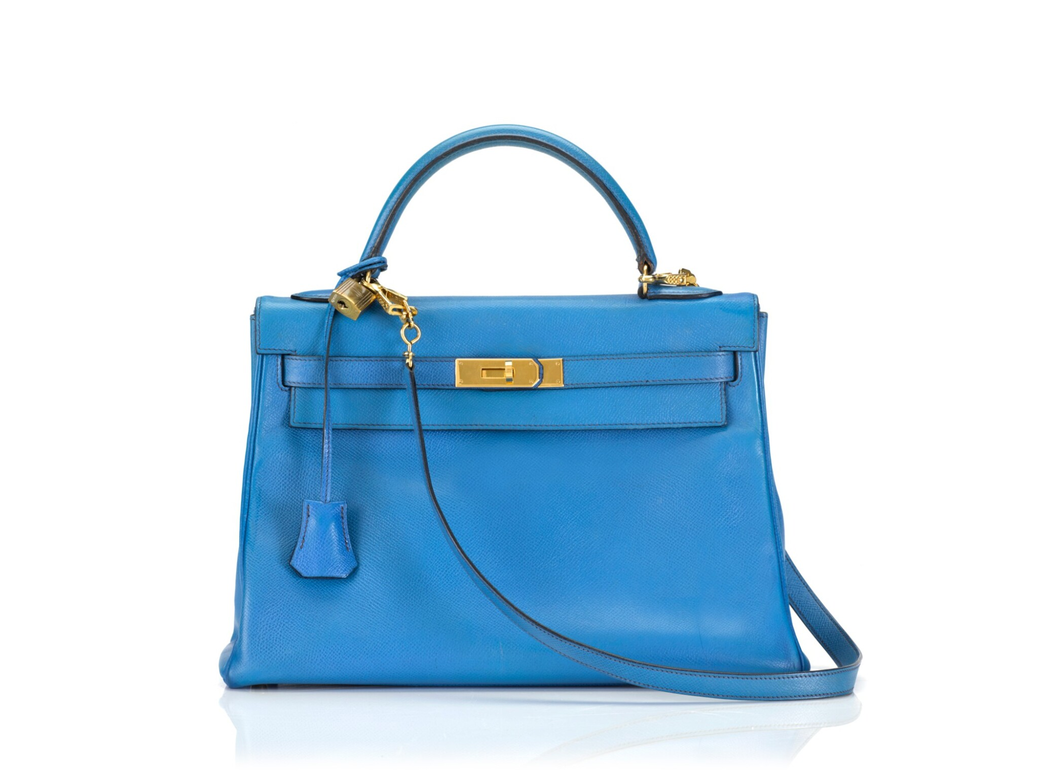 View full screen - View 1 of Lot 16. KELLY 32 RETOURNE BLUE FRANCE COLOUR IN COURCHEVEL LEATHER WITH GOLD HARDWARE. HERMÈS, 1992 .