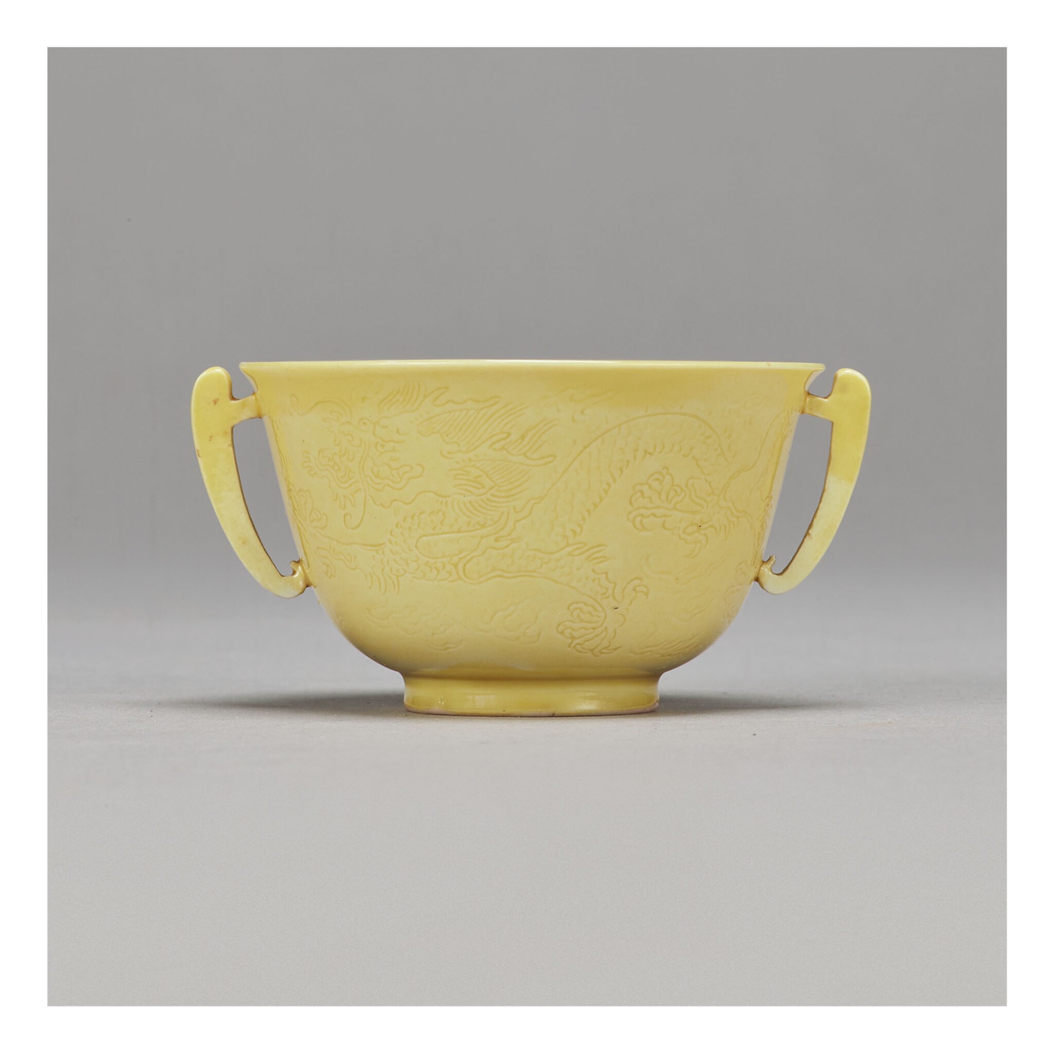View full screen - View 1 of Lot 101. A FINE INCISED YELLOW-GLAZED 'DRAGON' HANDLED CUP,  KANGXI MARK AND PERIOD.
