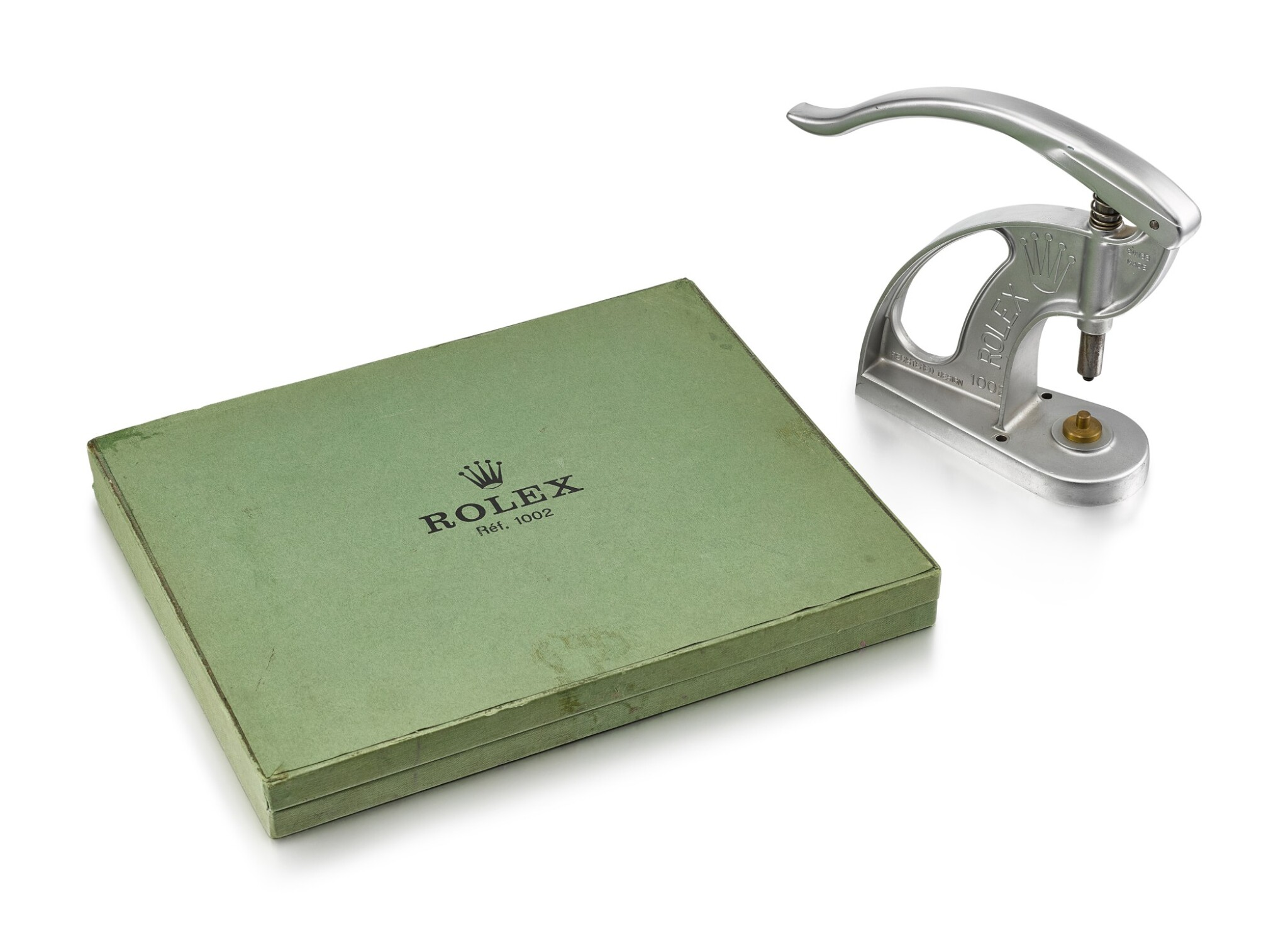 View 1 of Lot 8107. ROLEX | REFERENCE 1002, A STAINLESS STEEL STAKING TOOL FOR BEZELS AND CRYSTALS, CIRCA 1965 AND 23 BRASS JIGS AND ORIGINAL FITTED BOX, CIRCA 1981.