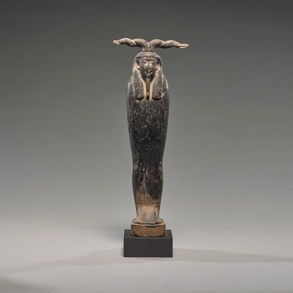 AN EGYPTIAN BITUMEN PAINTED WOOD FIGURE OF PTAH-SOKAR-OSIRIS, PTOLEMAIC PERIOD, 305-30 B.C.