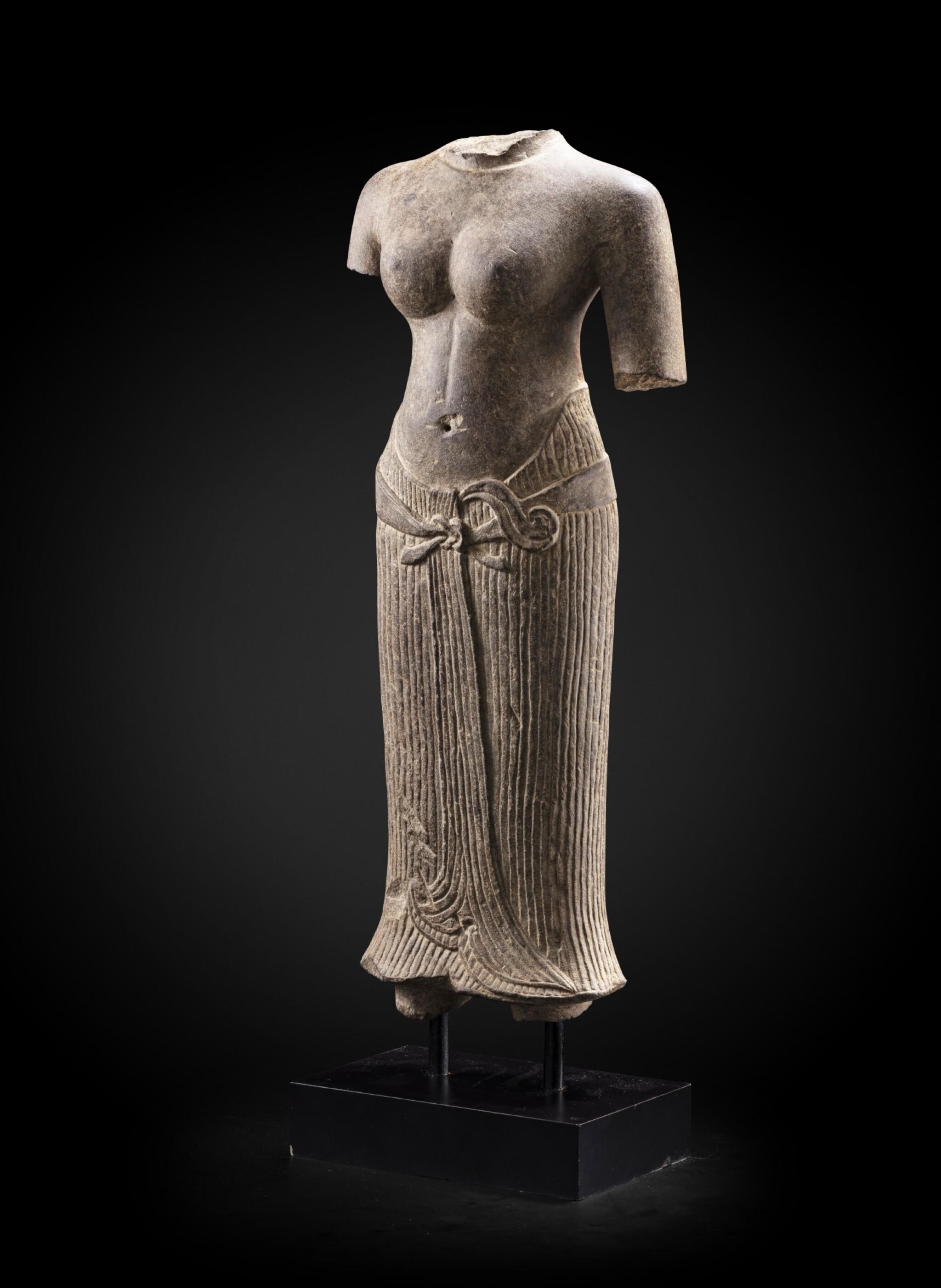 View full screen - View 1 of Lot 236. A grey sandstone torso of a female divinity Khmer art, Baphuon style, circa 11th Century | 高棉藝術 約十一世紀 巴普昂式砂岩雕女神立像殘件.