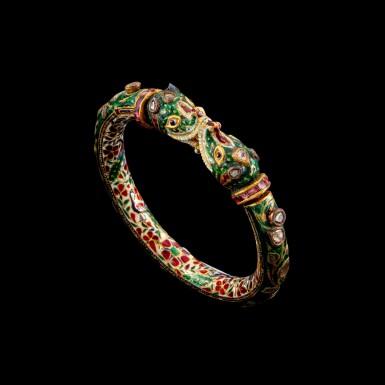 View 1. Thumbnail of Lot 1023. A gem-set and enamelled 'Makara' bracelet, kada Jaipur, North India, 19th century   十九世紀 北印度齋浦爾 金嵌鑽石、紅寶摩羯首手鐲 內飾琺瑯彩穿花孔雀紋.