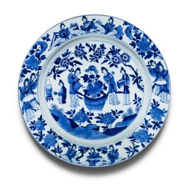 View 1. Thumbnail of Lot 21. Grande plat en porcelaine bleu blanc Dynastie Qing, époque Kangxi   清康熙 青花仕女賞荷圖折沿盤  《大明成化年製》仿款   A large blue and white 'Literati' dish, Qing Dynasty, Kangxi period.