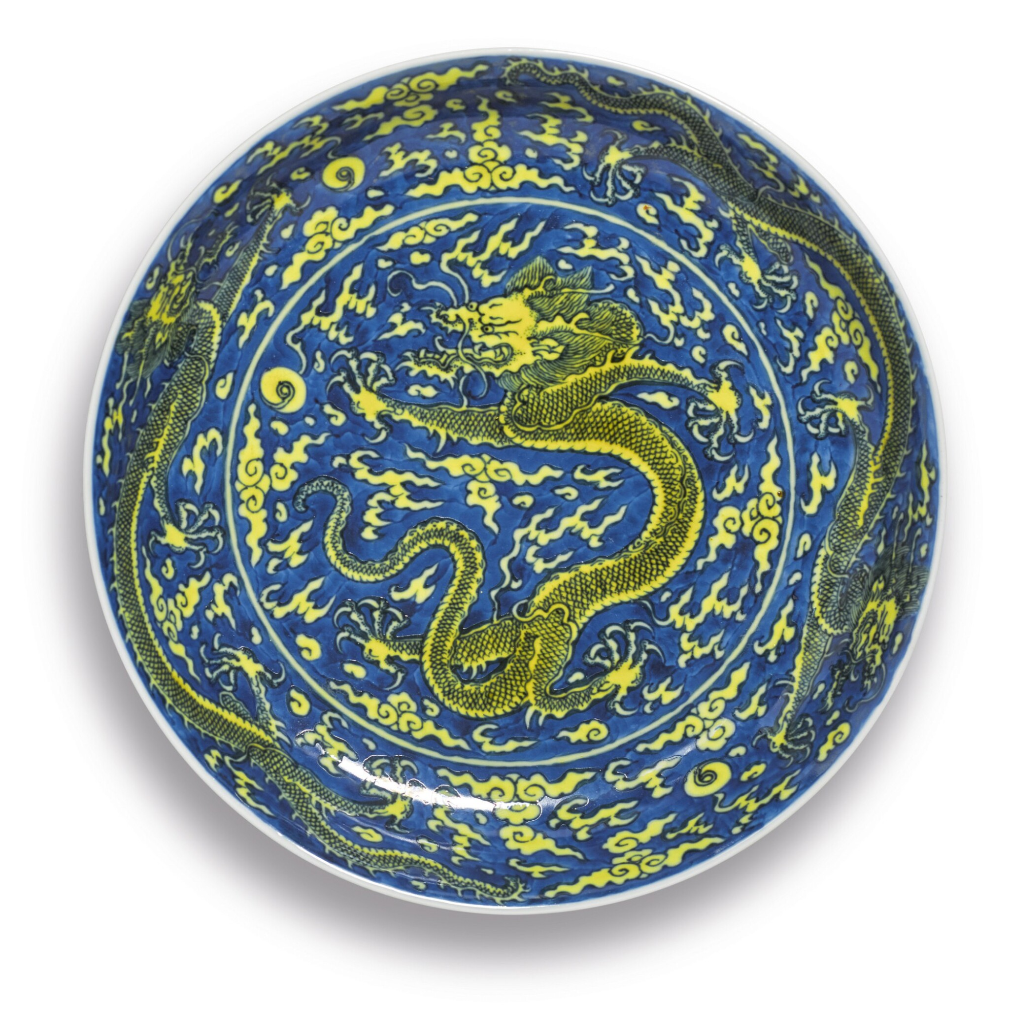 View 1 of Lot 561. A FINE YELLOW-ENAMELED AND BLUE-GROUND 'DRAGON' DISH,  KANGXI MARK AND PERIOD.