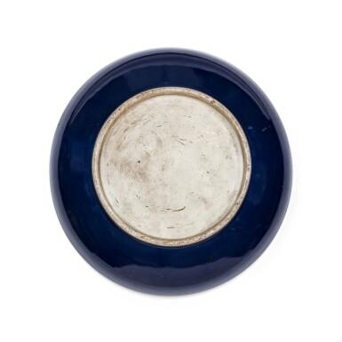 View 3. Thumbnail of Lot 17. Grand plat en porcelaine monochrome bleu Dynastie Qing, XVIIIE siècle   清十八世紀 灑藍釉圓盤   A large sacrificial blue-glazed charger, Qing Dynasty, 18th century.