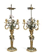 A PAIR OF LOUIS XV STYLE GILT BRONZE AND TOLE PEINTE CANDELABRA WITH POLYCHROME PORCELAIN FLOWERS, MOUNTED AS LAMPS