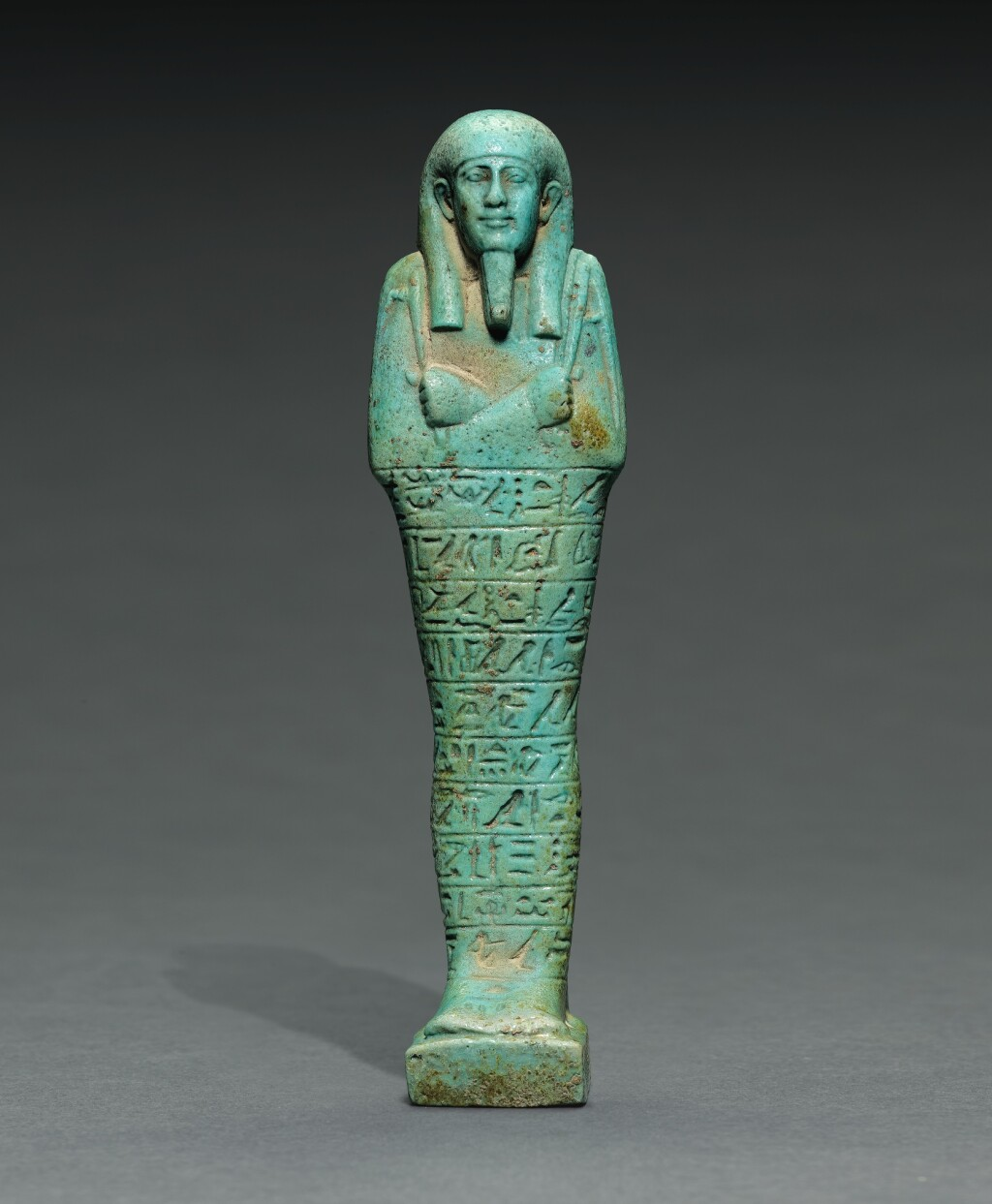 AN EGYPTIAN TURQUOISE FAIENCE USHABTI OF TJAI-NE-HEBU, ADMIRAL OF THE ROYAL FLEET, 26TH DYNASTY, REIGN OF AMASIS, 570-526 B.C.