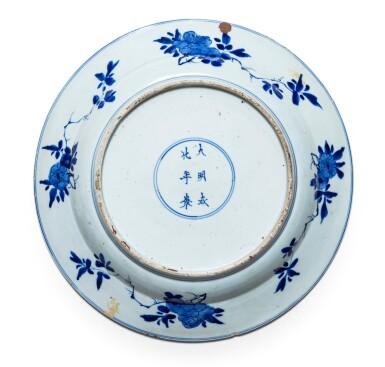View 2. Thumbnail of Lot 21. Grande plat en porcelaine bleu blanc Dynastie Qing, époque Kangxi   清康熙 青花仕女賞荷圖折沿盤  《大明成化年製》仿款   A large blue and white 'Literati' dish, Qing Dynasty, Kangxi period.