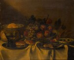 FOLLOWER OF FRANS YKENS | A still life witha fruit bowl, bread rolls, and a wine glass on a table
