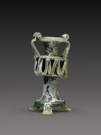 View 2. Thumbnail of Lot 8. A Roman Green Glass Unguentarium, circa 4th century A.D..