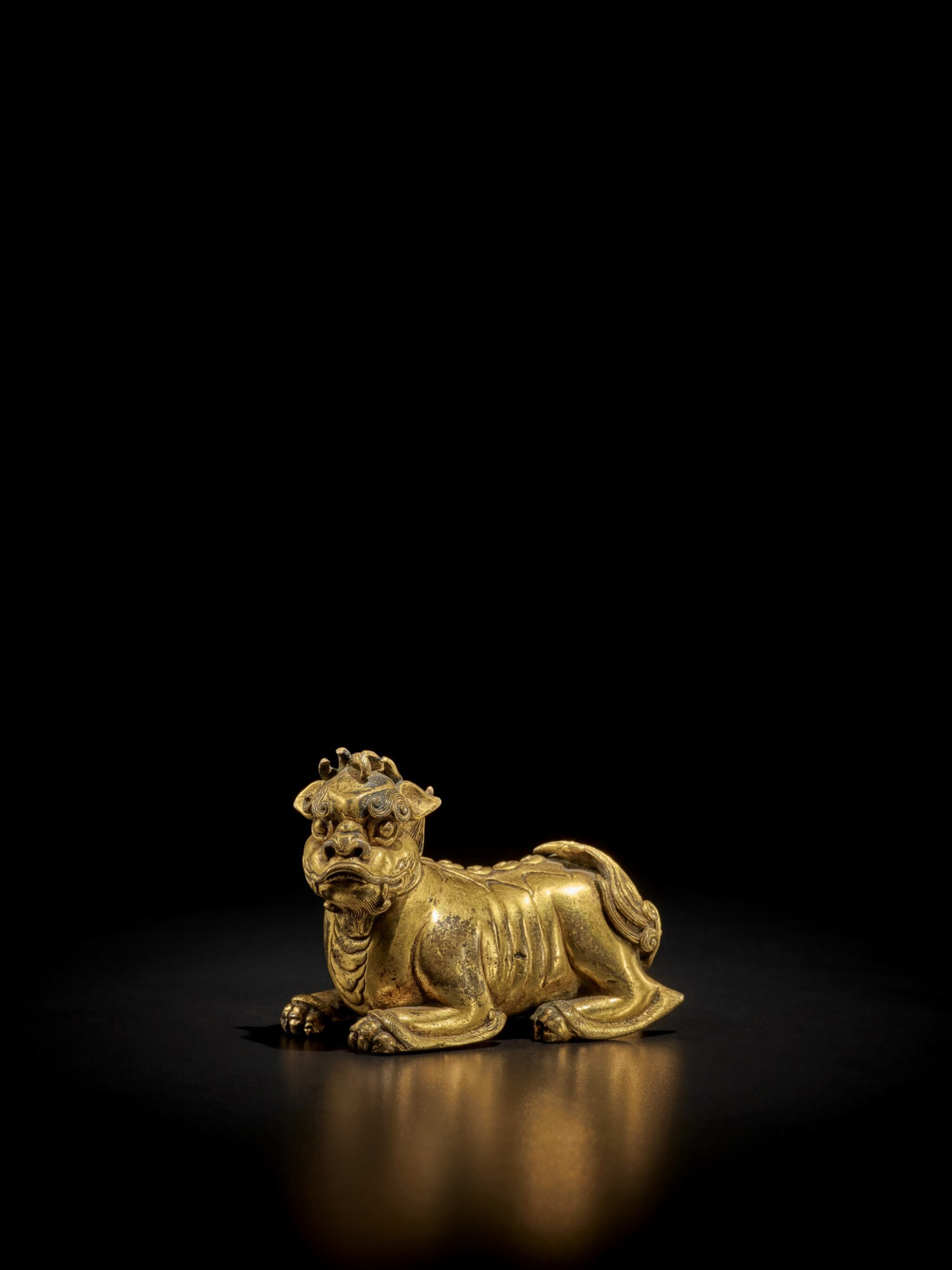 View full screen - View 1 of Lot 125. A gilt-bronze 'mythical beast' weight, Ming dynasty | 明 銅鎏金瑞獸形鎮.